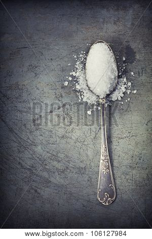 silver spoon filled with salt on rustick background
