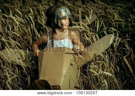 Little dreamer girl playing with a cardboard airplane in the wheat field. Childhood. Fantasy, imagination.