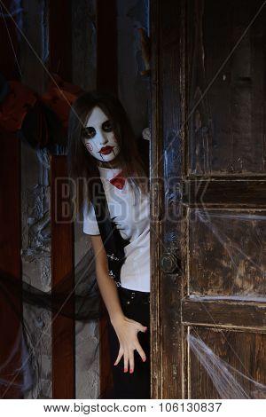 Girl In Makeup Looks From Behind The Door