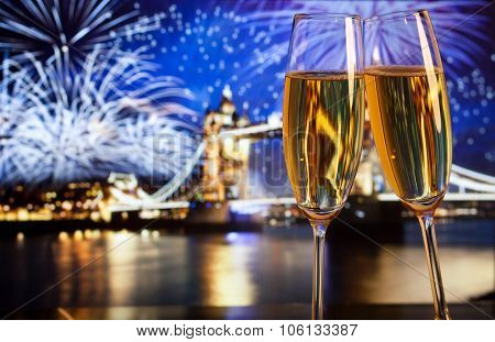 New Year celebration in the city - champagne glasses and Tower bridge with fireworks in the background