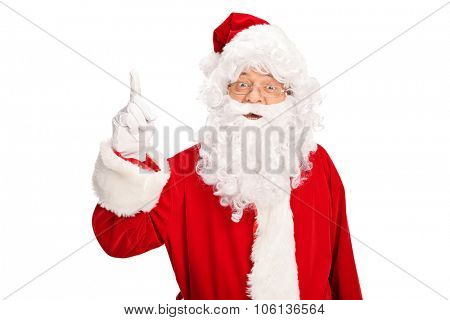 Santa Claus looking at the camera and pointing up with his finger isolated on white background