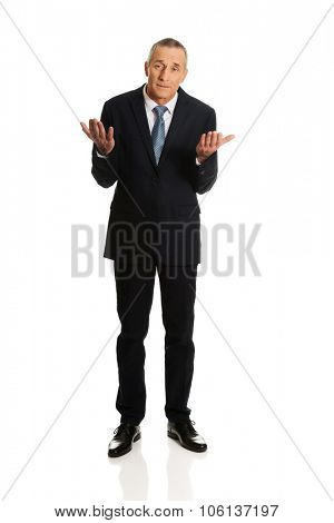 Full length businessman making undecided gesture.