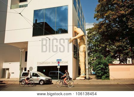 Cyclists Drive Past The Giant Sculpture Of A Peeping Man