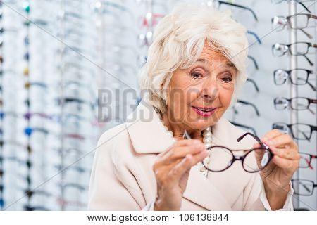 Senior Woman Trying On Eyeglasses