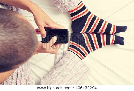 high-angle shot of a young caucasian man wearing pajamas and colorful striped socks using a smartphone in bed