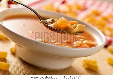 closeup of a bowl with minestrone, a typical italian soup, with vegetables and pasta, on a set table