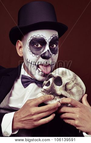 a young man with mexican calaveras makeup, wearing top hat and bow tie, licks a scary skull