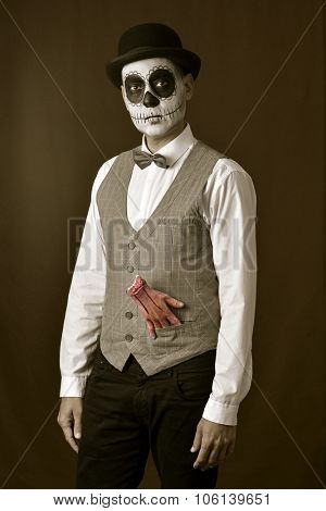 a man with mexican calaveras makeup, wearing bow tie and bowler hat, with an amputated bloody hand in the pocket of his vest