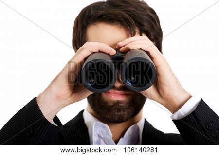Young handsome businessman looking through binoculars.