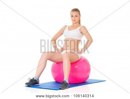 Young happy woman doing fitness exercise with fitness-ball, isolated on white background