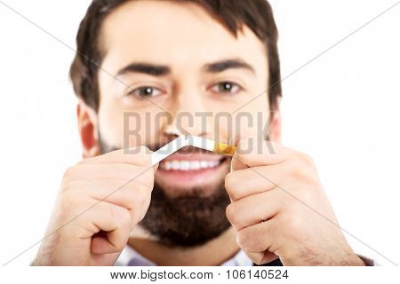 Businessman breaking a cigarette. Stop smoking concept.