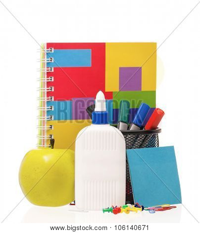 Office supplies - markers, glue bottle, exercise book and green apple isolated on white background