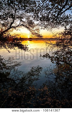 Sunset At The Lake, View From The Forest Edge With Reflections And Autumn Leaves On The Water
