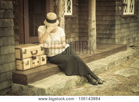 Distressed 1920s Dressed Girl Next To Suitcases on Porch with Vintage Effect Added.