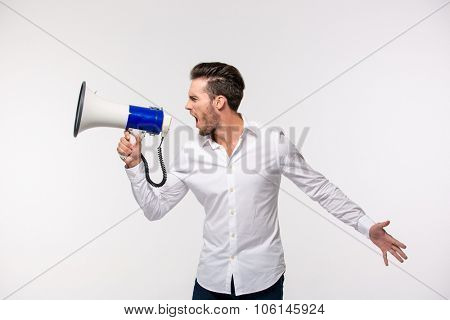 Portrait of a man screaming in megaphone isolated on a white background