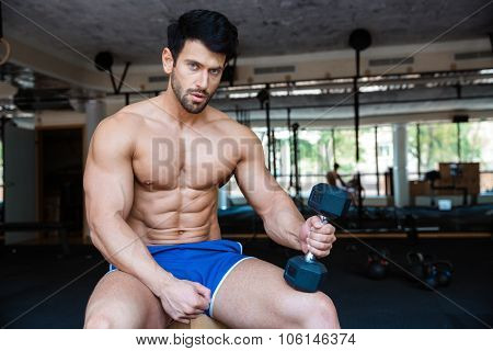 Portrait of a serious muscular man holding dumbbell in fitness gym and looking at camera