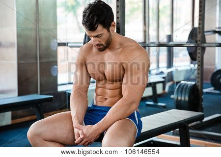Portrait of a muscular man sitting on the bench at fitness gym