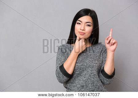 Beautiful serious asian girl in gray jumper pointing up with one finger and having an idea