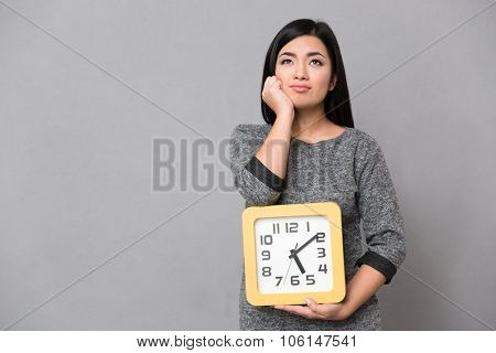 Beautiful asian young woman in gray jumper waiting and holding big clock