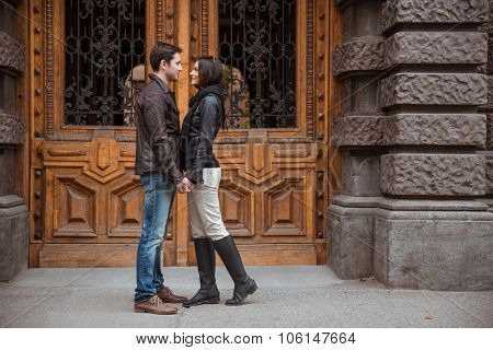 Portrait of romantic couple standing outdoors with old wooden door on bacground