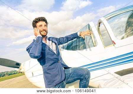 Young Handsome Man Talking With Mobile Smart Phone At Private Airplane - Modern Business Concept