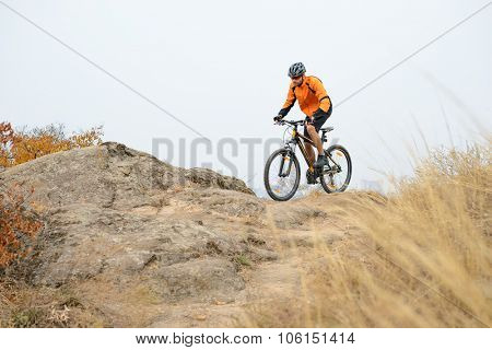 Cyclist in Orange Wear Riding Bike on the Beautiful Autumn Mountain Trail