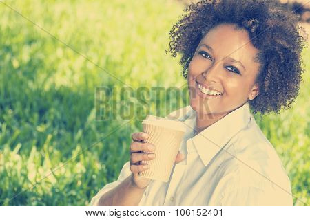 Instagram style photograph of a beautiful young mixed race black African American woman smiling and drinking a takeaway cup of coffee outside