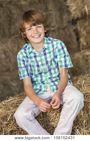 Young happy smiling boy wearing a plaid shirt and sitting in barn on bales of hay or straw