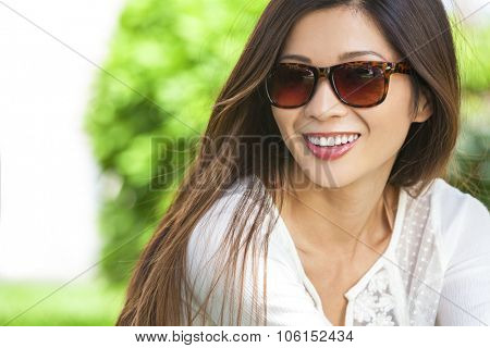 Outdoor portrait of a beautiful young Chinese Asian young woman or girl with perfect teeth wearing sunglasses