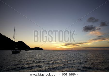 Sailing yacht in open sea on beautiful sunset sky background
