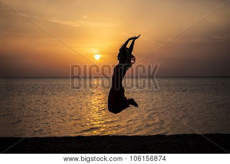 Woman Jumping Beautiful Silhouette Against The Sea And Dawn
