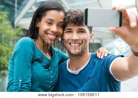 Closeup shot of young couple take selfie outdoor. Happy young man and woman smiling and photographing self in the city center. Happy young couple embracing and taking selfie with smartphone.