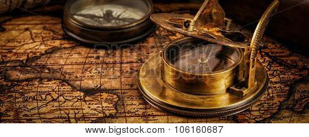 Travel geography navigation concept background - letterbox panorama of old vintage retro compass with sundial and spyglass on ancient world map with copyspace