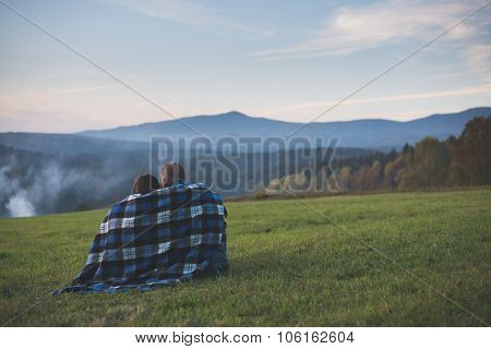 Traveler couple watching landscape and mountains under a blanket