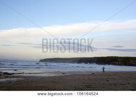 Woman Walking At Rocky Cold Beach