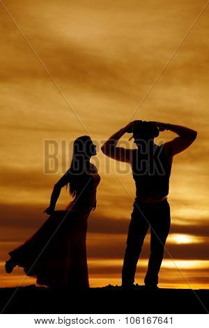 Silhouette Cowboy And Woman In Sunset Face Each Other