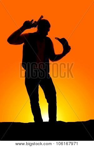 Silhouette Of A Cowboy With A Pistol By Head Hat In Hand