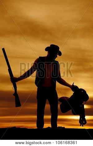Silhouette Of Cowboy In Sunset Holding Gun And Saddle