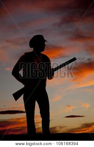 Silhouette Of Cowboy With Shotgun By Waist In Sunset