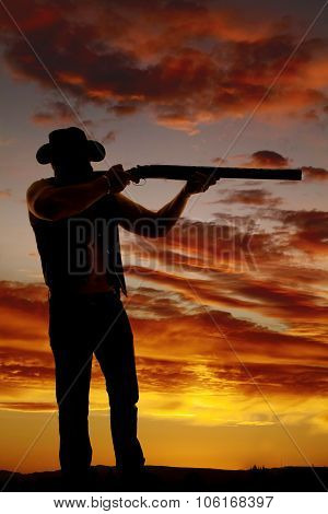 Silhouette Of Cowboy With Shotgun Aimed In Sunset
