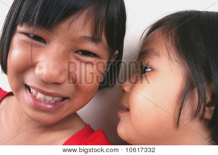 Two young asian kids whispering.