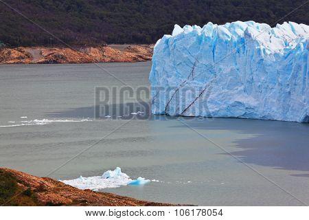 Giant lake Perito Moreno glacier. White-blue ice massif multimeter height rises over the lake Argentino