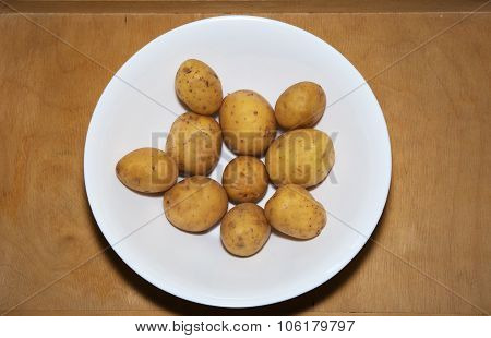 Bowl Of Raw Potatoes On A Wooden Table