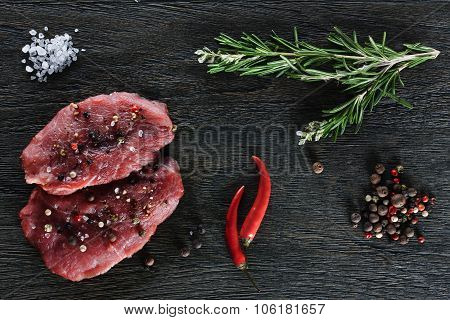 Two garnished raw beef steaks