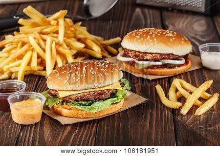 Two Burgers With Grilled Meat With French Fries On Craft Paper On Wooden Surface In Kitchen. Fast Fo