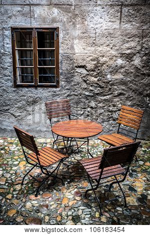 Abandoned Chairs And Table With Dark Window