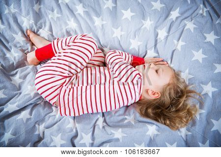 Cute Little Girl Sleeps In Pajames On Bed