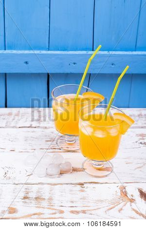 Orange juice in a glass with ice on a white wooden table