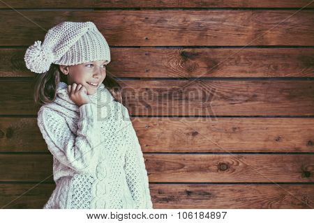 Cute 9 years old girl wearing knitted autumn or winter clothing posing over wooden background