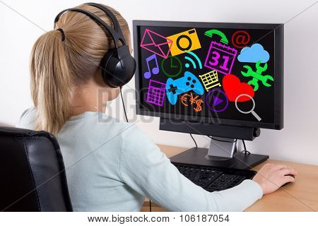 Internet Concept - Back View Of Young Woman Using A Computer And Listening Music